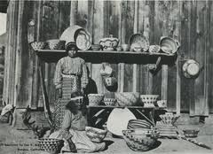 """""""An old Indian woman selling the artifacts of her tribe to passers-by; peaceful adaption to collective needs"""""""