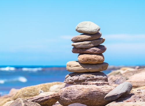 A photo of stacked rocks next to the ocean